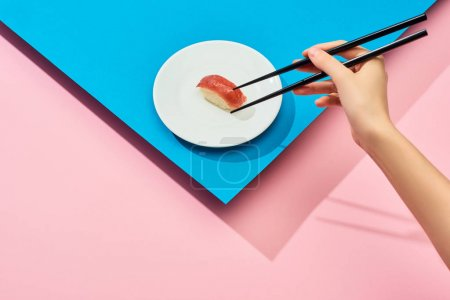 Photo for Cropped view of woman eating fresh nigiri with tuna with chopsticks on blue, pink background - Royalty Free Image