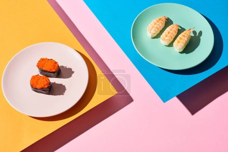 Photo for Fresh nigiri with shrimps and red caviar on blue, pink, orange background - Royalty Free Image