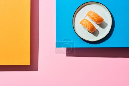 Photo for Top view of fresh nigiri with salmon on blue, pink, orange background - Royalty Free Image