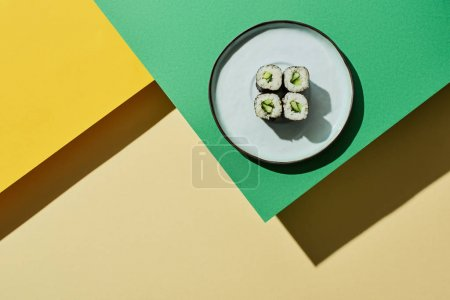 Photo for Top view of fresh nigiri with cucumber on green and yellow surface - Royalty Free Image