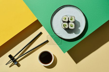 Photo for Top view of fresh nigiri with cucumber near soy sauce and chopsticks on green and yellow surface - Royalty Free Image