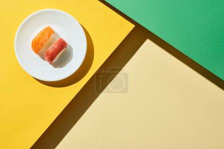 Photo pour Top vue de nigiri frais avec saumon et thon sur les surfaces verte et jaune - image libre de droit