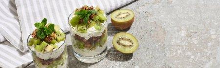 Photo pour Granola frais avec kiwi et yaourt sur une surface en béton gris avec serviette rayée, vue panoramique - image libre de droit
