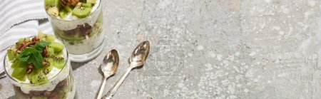 Photo for Fresh granola with kiwi and yogurt on grey concrete surface with striped napkin and spoons, panoramic shot - Royalty Free Image