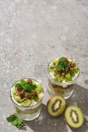 Photo for Fresh granola with kiwi and yogurt on grey concrete surface - Royalty Free Image