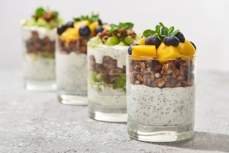 Photo for Selective focus of fresh granola with kiwi and canned peach with blueberries on grey concrete surface isolated on grey - Royalty Free Image