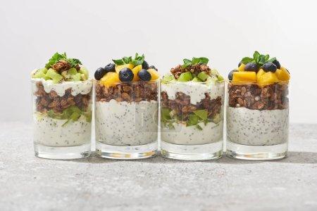 Foto de Granola fresca con kiwi y melocotón enlatado con arándanos en superficie gris de hormigón aislado en gris. - Imagen libre de derechos