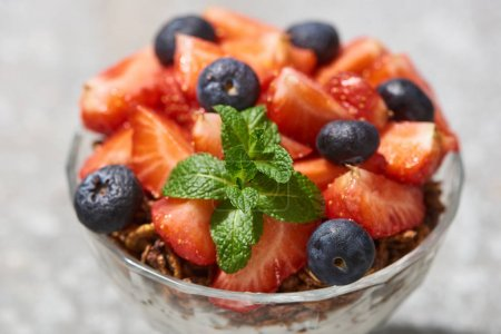 Photo for Close up view of delicious granola with berries and mint on grey concrete surface - Royalty Free Image