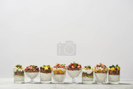 Photo for Delicious granola in glasses with fruits and berries isolated on white - Royalty Free Image