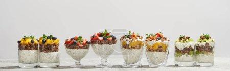Foto de Deliciosa granola en gafas con frutas y bayas aisladas en blanco, tiro panorámico. - Imagen libre de derechos