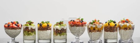 Photo for Delicious granola in glasses with fruits and berries isolated on white, panoramic shot - Royalty Free Image