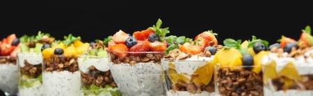 Photo for Selective focus of fresh granola with fresh fruits and berries isolated on black, panoramic shot - Royalty Free Image