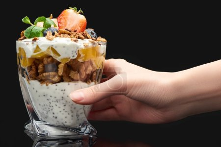 Photo for Cropped view of woman holding glass with fresh granola with canned peach, berries, walnuts and chia seeds isolated on black - Royalty Free Image