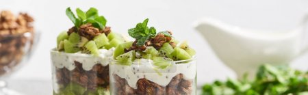 Photo for Selective focus of fresh granola with kiwi and yogurt isolated on grey - Royalty Free Image