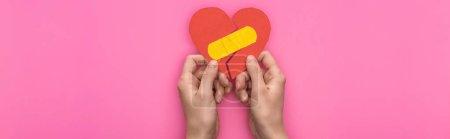 Foto de Vista rota de sostener el corazón de papel roto con parches aislados sobre fondo rosado, tiro panorámico. - Imagen libre de derechos