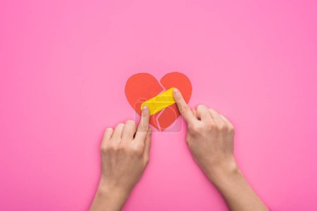 Photo for Cropped view of woman putting patch on broken paper heart isolated on pink background - Royalty Free Image