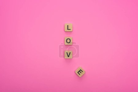 Photo pour Top view of love lettering on wooden cubes isolated on pink background - image libre de droit