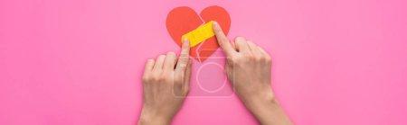 Foto de Vista rota de la mujer poniendo parches en papel roto corazón aislado en el fondo rosa, tiro panorámico. - Imagen libre de derechos