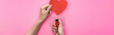 Photo for Cropped view of woman lighting up empty red paper heart with lighter isolated on pink, panoramic shot - Royalty Free Image