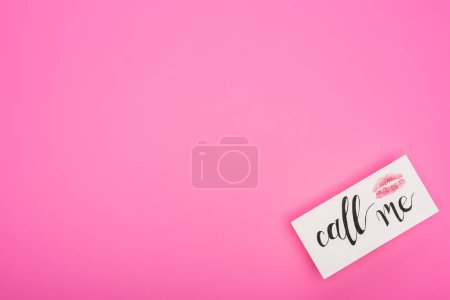 Photo pour Top view of card with lip print and call me lettering isolated on pink - image libre de droit