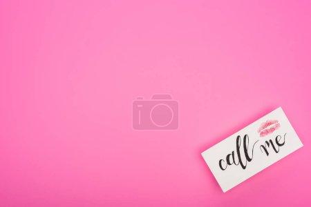 Foto de Vistas superiores de la tarjeta con impresión de labios y llámenos con letras aisladas en rosa. - Imagen libre de derechos