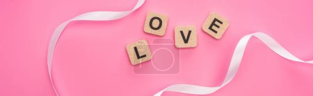 Photo for Top view of curved ribbon and wooden blocks with love lettering isolated on pink, panoramic shot - Royalty Free Image