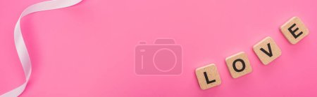 Photo pour Top view of ribbon and love lettering on wooden cubes isolated on pink, panoramic shot - image libre de droit
