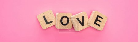 top view of love lettering on wooden cubes isolated on pink, panoramic shot