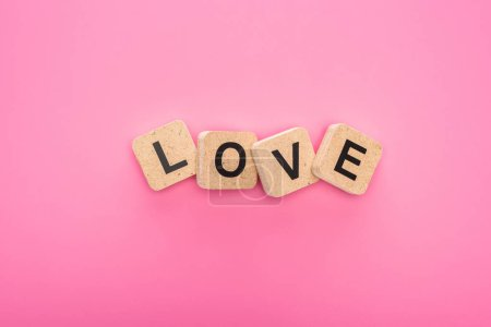 Photo pour Top view of love lettering on wooden cubes isolated on pink - image libre de droit