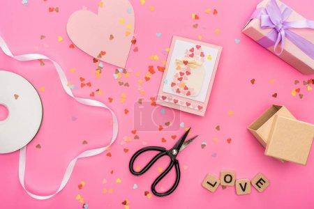 Foto de Visión superior de la confeti � n, disco compacto vacío, tijeras, cajas de regalo, tarjeta de felicitación y carta de amor en cubos de madera de fondo rosa. - Imagen libre de derechos