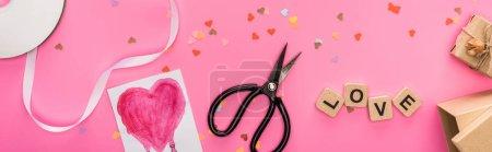 Photo pour Vue du dessus des confettis de Saint-Valentin, disque compact vide, ciseaux, boîtes cadeaux, carte de vœux et lettrage d'amour sur des cubes en bois sur fond rose, prise de vue panoramique - image libre de droit