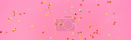 Photo pour Top view of valentines confetti scattered on pink background, panoramic shot - image libre de droit
