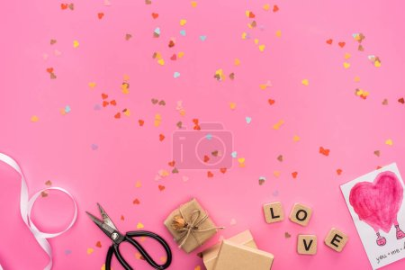 Foto de Visión superior de la casa, disco compacto vacío, tijeras, cajas de regalo, tarjeta de felicitación y cubos con carta de amor sobre fondo rosa. - Imagen libre de derechos