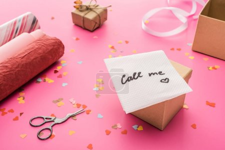 Photo pour Valentines confetti, scissors, card with call me lettering, wrapping paper, gift box on pink background - image libre de droit