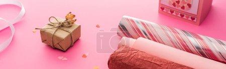 Foto de Camisetas confeti, papel de embalaje, caja de regalo en fondo rosa, tiro panorámico. - Imagen libre de derechos