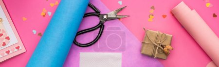Photo for Top view of valentines decoration, wrapping paper, gift box, scissors on pink background, panoramic shot - Royalty Free Image