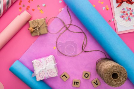 Photo pour Top view of valentines decoration, wraping paper, twine, gift boxes, greeting card and love lettering on wooden cubes on pink background - image libre de droit