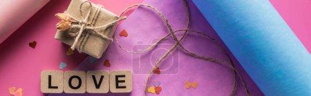 Foto de Vista superior de la decoración, papel de envolver, gemelos, caja de regalo y carta de amor en cubos de madera de fondo rosa, tiro panorámico. - Imagen libre de derechos