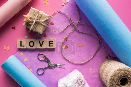 Foto de Vista superior de la decoración, tijeras, papel de envolver, gemelos, cajas de regalo y carta de amor en cubos de madera de fondo rosa. - Imagen libre de derechos