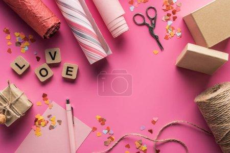 Foto de Vista superior de la decoración, tijeras, caja de regalo, gemelos, papel de envolver y carta de amor en cubos de madera de fondo rosa. - Imagen libre de derechos
