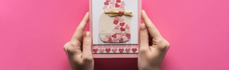 Photo pour Cropped view of woman holding valentines greeting card isolated on pink, panoramic shot - image libre de droit