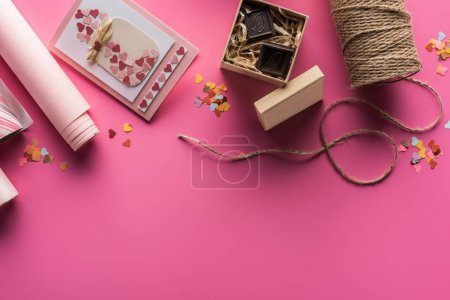 Photo for Top view of valentines decoration, wrapping paper, twine, gift box with chocolate, greeting card on pink background - Royalty Free Image