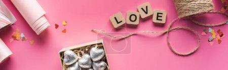 Foto de Vistas superiores del papel de envolver, gemelos, caja de regalo con corazones plateados y carta de amor sobre cubos de madera en fondo rosa, tiro panorámico. - Imagen libre de derechos