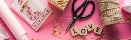 Photo pour Top view of valentines decoration, scissors, wrapping paper, twine, gift, greeting card and love lettering on wooden cubes on pink background, panoramic shot - image libre de droit