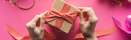 Foto de Vista parcial de la caja de regalo decorada por mujeres con cinta sobre fondo rosa, tiro panorámico. - Imagen libre de derechos