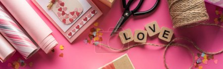 Photo for Top view of valentines decoration, scissors, wrapping paper, twine, gift, greeting card and love lettering on wooden cubes on pink background, panoramic shot - Royalty Free Image