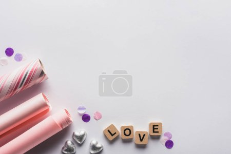 Photo for Top view of silver hearts, wrapping paper and cubes with love lettering on white background - Royalty Free Image