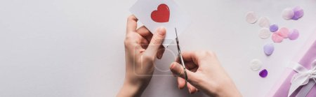 Photo for Cropped view of woman cutting out heart with scissors near valentines gift on white background, panoramic shot - Royalty Free Image