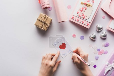 Photo for Cropped view of woman writing on card near valentines decoration, gifts, hearts and wrapping paper on white background - Royalty Free Image
