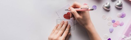 Photo for Cropped view of woman writing on valentines card with heart on white background, panoramic shot - Royalty Free Image
